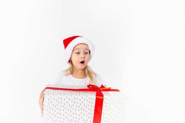 Weinig glimlachend meisje die in de hoed van de santahelper witte gift met rood lint op wit geïsoleerde achtergrond houden. kerstmis, winter, geluk concept.