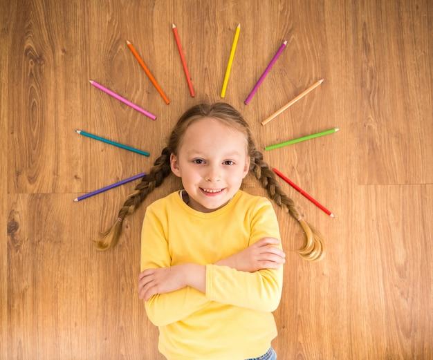 Weinig glimlachend meisje die in gele trui op de vloer leggen.