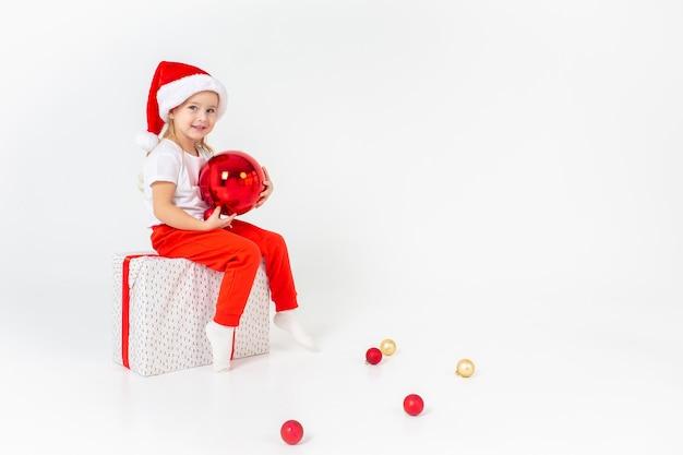 Weinig glimlachend meisje in de hoedenzitting van de santahelper op een giftbox met rood lint en holdings rode kerstmisbal, wit geïsoleerde achtergrond. kerstmis, winter, geluk concept.