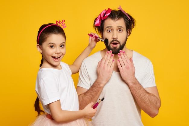 Weinig glimlachend meisje maakt gezicht van papa met borstel schoon.