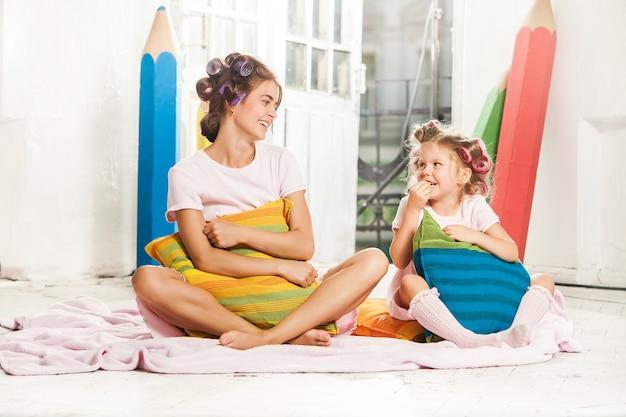 Weinig glimlachend meisje speelt met haar moeder op wit