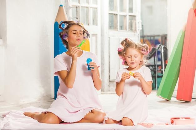 Weinig glimlachend meisje speelt met zeepbel en haar moeder op wit