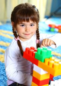 Weinig glimlachend meisje speelt thuis.