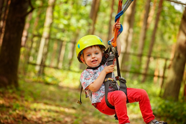 Weinig glimlachende kindjongen in avonturenpark in veiligheidsapparatuur in de zomerdag