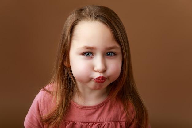 Weinig grappig meisje dat haar lippen in een kus uitrekt