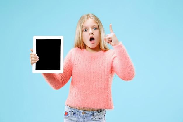 Weinig grappig meisje met tablet op blauwe studio.