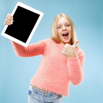 Weinig grappig meisje met tablet op blauwe studioachtergrond. ze laat iets zien en wijst naar het scherm Gratis Foto