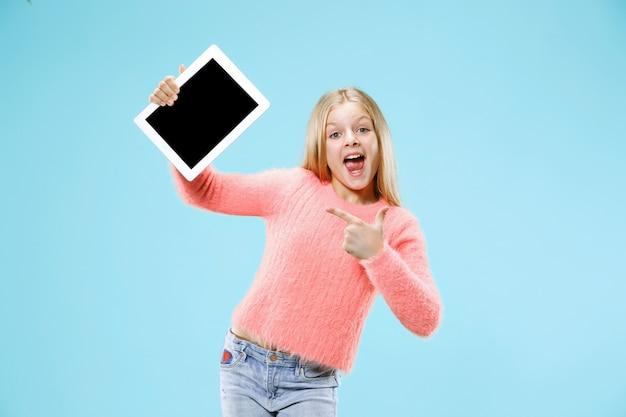 Weinig grappig meisje met tablet op blauwe studioachtergrond. ze laat iets zien en wijst naar het scherm.