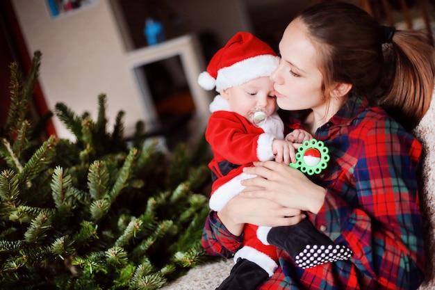 Weinig grappige baby verkleed als kerstman en jonge mooie moeder naast de kerstboom.