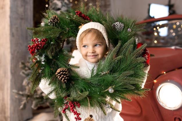 Weinig grappige jongen die met de kroon van kerstmis speelt.