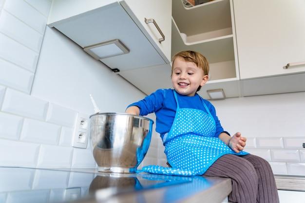 Weinig grappige schattige peuterjongen die de binnenlandse appeltaart van het keukenschort dragen