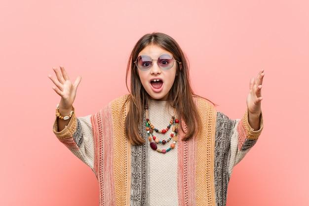 Weinig hippie meisje ontvangt een aangename verrassing, opgewonden en verhogen handen