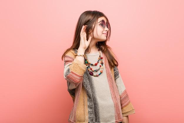 Weinig hippie meisje probeert te luisteren naar een roddel.