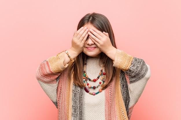 Weinig hippiemeisje behandelt ogen met handen, glimlachen die ruim op een verrassing wachten.