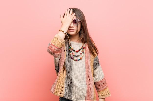 Weinig hippiemeisje dat iets vergeet, voorhoofd met palm slaat en ogen sluit
