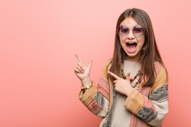 Weinig hippiemeisje dat met wijsvingers op een exemplaarruimte richt, opwinding en wens uitdrukt