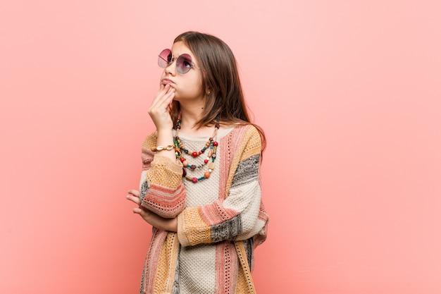 Weinig hippiemeisje die zijdelings met twijfelachtige en sceptische uitdrukking kijken.