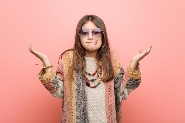 Weinig hippiemeisje verward en twijfelachtig die de handen opheffen