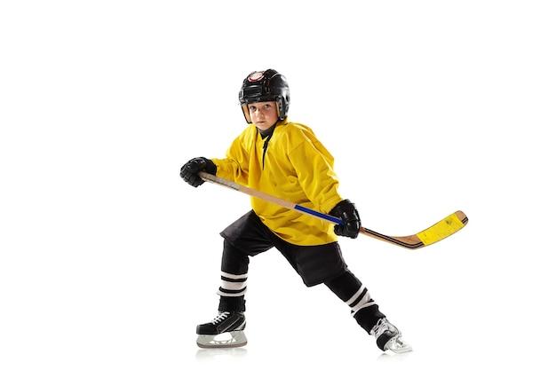 Weinig hockeyspeler met de stok op ijsbaan en wit