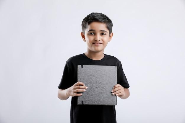 Weinig indische / aziatische jongen die notaboek toont