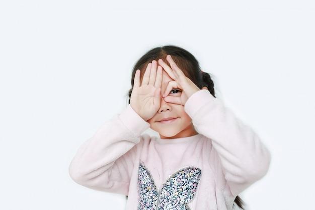 Weinig jong geitjemeisje met één handglazen en sluit voor haar geïsoleerde ogen