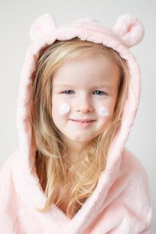 Weinig jong meisje dat bevochtigende room op haar gezicht toepast. huidverzorging en schoonheid concept