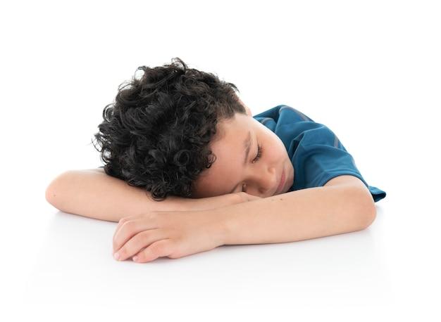 Weinig jonge exausted luie jongen in slaap op witte lijst aangaande witte achtergrond