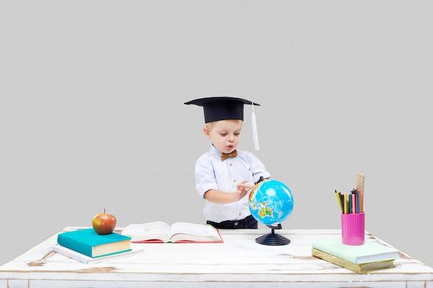 Weinig jongen bestudeert terwijl het dragen van een graduatie glb op een grijze geïsoleerde muur