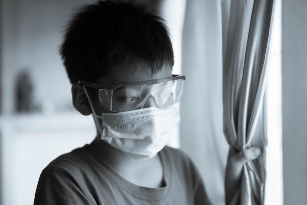 Weinig jongen blijft thuis quarantainetijd kijkend buiten uit het venster