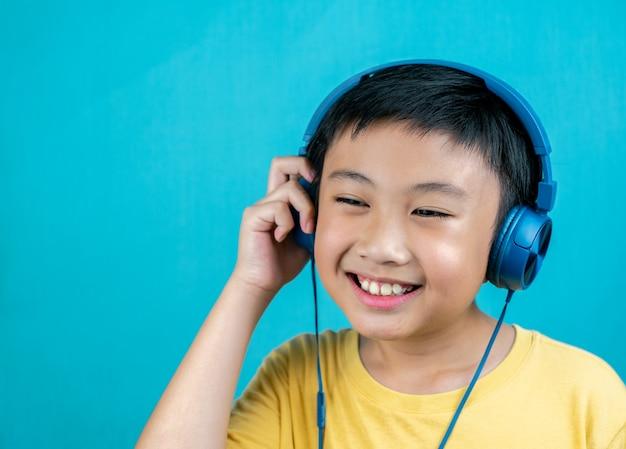 Weinig jongen die aan muziek op blauwe achtergrond luistert