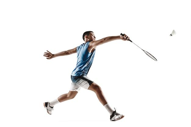 Weinig jongen die badminton speelt dat op witte muur wordt geïsoleerd