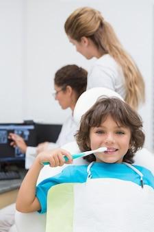 Weinig jongen die bij camera met moeder en tandarts op achtergrond glimlacht