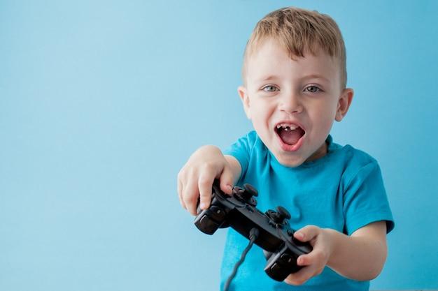 Weinig jongen die blauwe kleren draagt houdt joystick in de hand