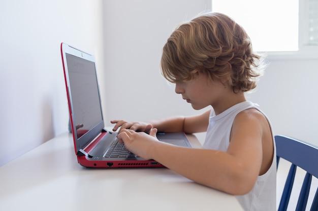 Weinig jongen die computer met behulp van om in zijn slaapkamer te bestuderen. lagere schoolleeftijd.