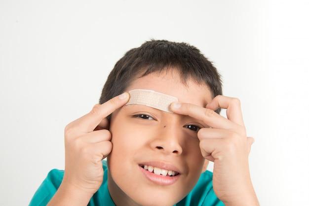 Weinig jongen die de stok van de pleisterband op zijn eyebow gebruikt