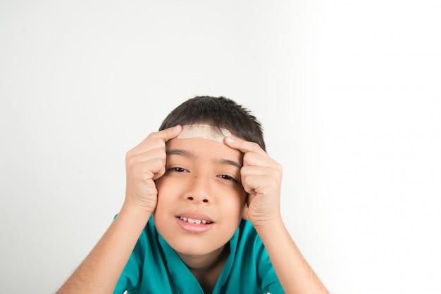Weinig jongen die de stok van de pleisterband op zijn hoofd gebruikt