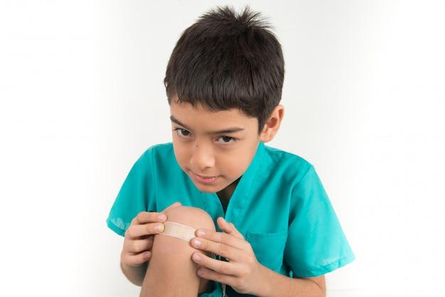 Weinig jongen die de stok van de pleisterband op zijn knie gebruikt
