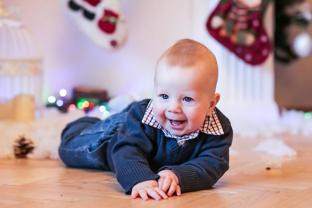 Weinig jongen die dichtbij de open haard en kerstmisgiften glimlacht