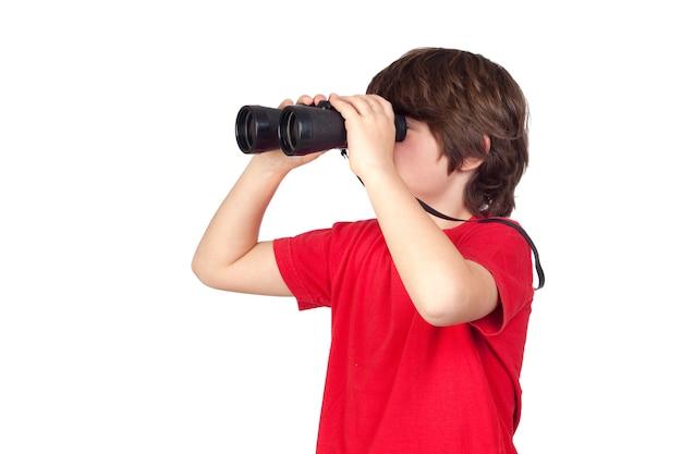 Weinig jongen die door verrekijkers kijkt die op witte achtergrond worden geïsoleerd