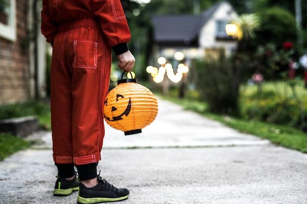 Weinig jongen die een halloween-lantaarn houdt
