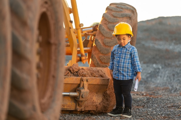 Weinig jongen die een helm draagt, droomconcept, wil een toekomstige ingenieur zijn.