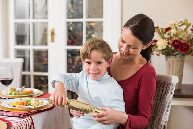 Weinig jongen die een kerstmiscracker met zijn moeder trekt