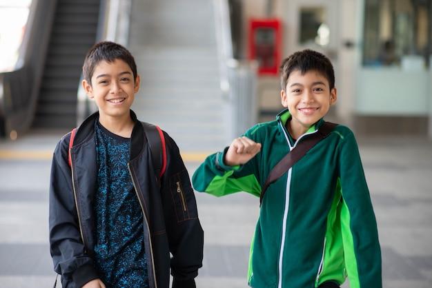 Weinig jongen die elektrisch kaartje koopt en in het openbare hemeltreinstation loopt met familie