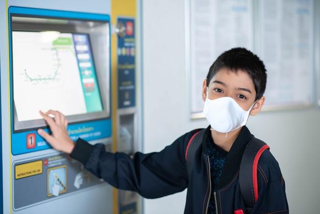 Weinig jongen die elektrisch kaartje kopen en in het openbare hemelstation lopen met familie