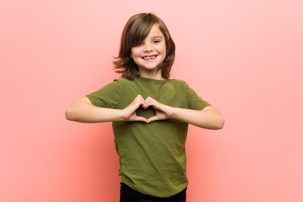 Weinig jongen die en een hartvorm met handen glimlacht toont.