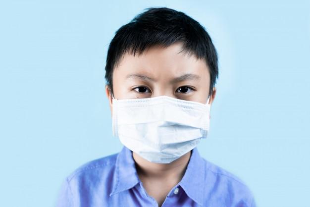 Weinig jongen die gezonde maskers draagt voor beschermt virus