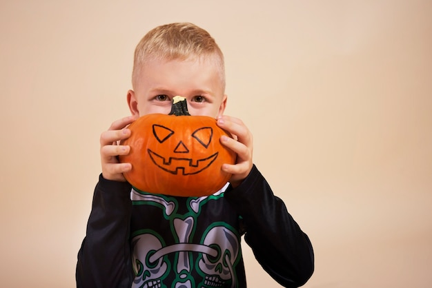 Weinig jongen die halloween-pompoen voor zijn gezicht houdt Gratis Foto