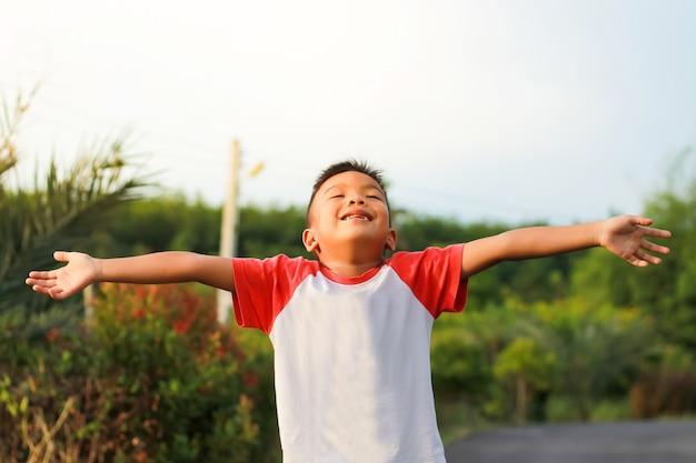 Weinig jongen die handen opheft omhoog en aan zonsondergang op hemel kijkt.