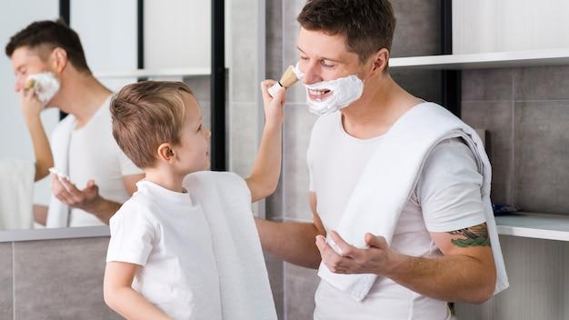 Weinig jongen die het scheerschuim op het gezicht van zijn vader met borstel in de badkamers toepassen