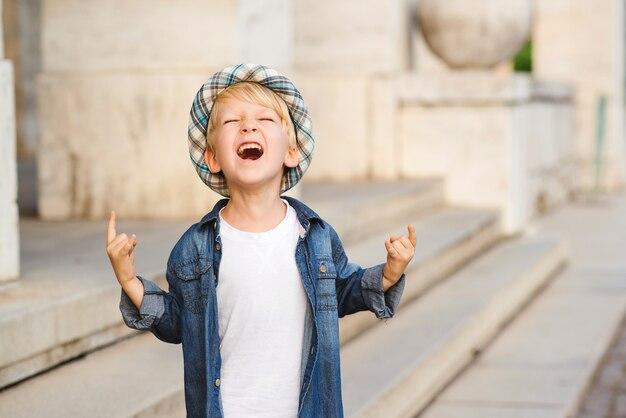Weinig jongen die het teken van de zwaar metaalrots buiten afschildert jeugd levensstijl concept.